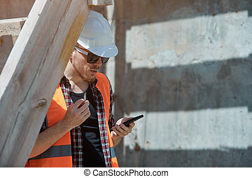 Construction site worker in a protective vest and hard hat, Smoking with a mobile phone in his hands