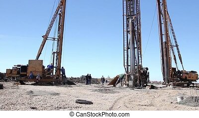 Construction site - Workers are managing pile driving...