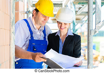 Construction Team with building plans on site
