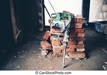 Construction tool, industrial jackhammer with demolition debris and bricks