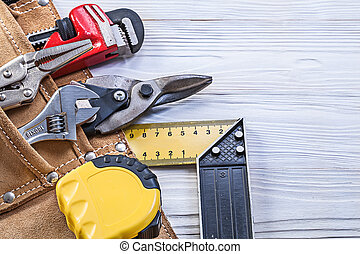 Construction tools in building belt on wooden board maintenance