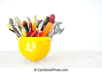 Construction tools in helmet over grunge background against empty white wall. Copy space.
