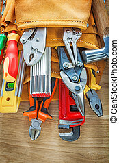 Construction tools in leather building belt on wood board