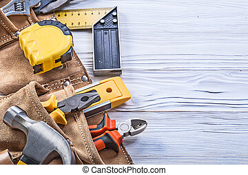 Construction tools in leather building belt on wooden board main