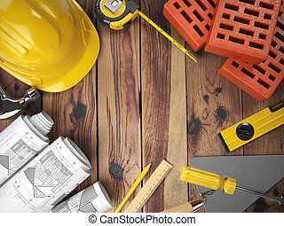 Construction tools on a wooden background. Hard helmet, bricks, trowel, drawing and level with space for text.