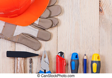Construction tools on wooden board top view.