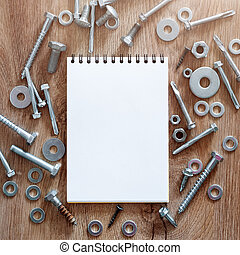 Construction tools. The screws, nuts and bolts arranged around blank spiral bound note book paper on wooden background. Repair, home improvement concept. Free space for text, top view, flat lay.