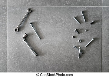 Construction tools. The screws, nuts and bolts on concrete background. Repair, home improvement concept. Space for text, top view, flat lay.