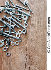 Construction tools. The screws, nuts and bolts on wooden background. Repair, home improvement concept. Free space for text, top view, flat lay.