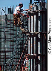 Two construction workers on a reinforced concrete pillar