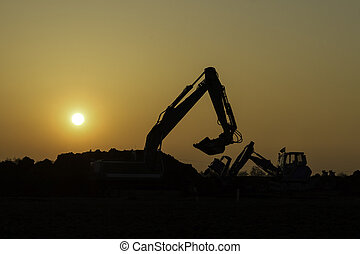 Construction vehicles in the sunset - You see the black...