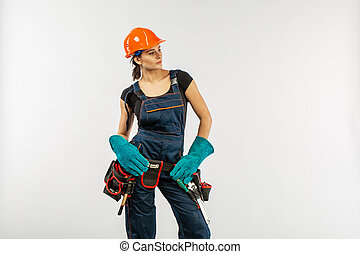 Construction work and home improvement jobs concept with a caucasian brunette mature woman wearing helmet or hard hat, tool belt and other safety equipment on white