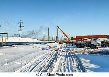 Construction work on pipe laying of pipeline into the trench using a crane