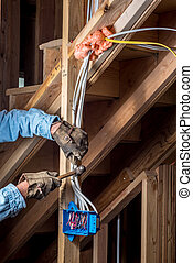 Construction worked adds brads to electrical wiring - ...