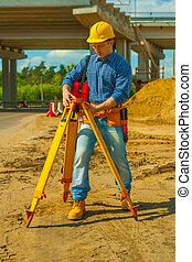 construction worker adjusting theodolite