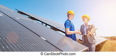 Construction worker and investor in solar power plant shaking hands
