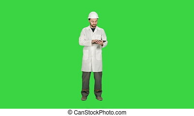 Construction worker and new building, man with safety helmet and using digital tablet computer on a Green Screen, Chroma Key.