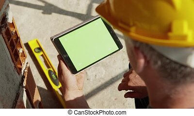 Construction worker and new building, adult man at work with safety helmet and using digital tablet computer for data entry. Part 8 of 8