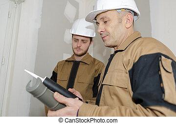 construction worker assembling silicone gun