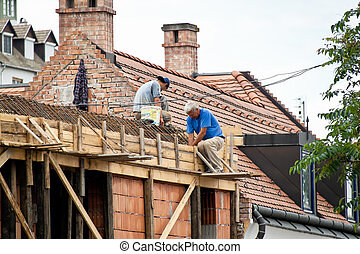 construction worker at roofing - two construction workers at...