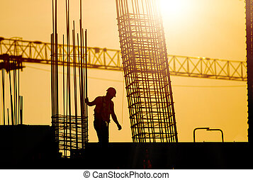 Construction worker at site in sunset