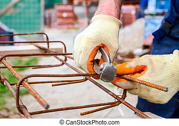 Construction worker binding rebar for reinforce concrete column at the building site.