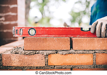 construction worker, bricklayer or mason laying bricks and creating walls. Detail of level tool