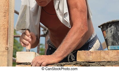 Construction worker bricklayer installing brick outdoors