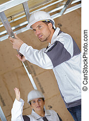 construction worker building ceiling frame