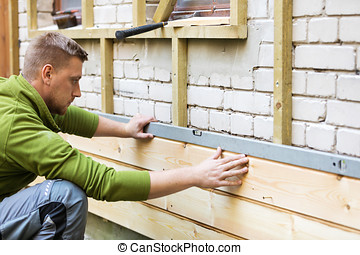 construction worker checking level of new house wood facade