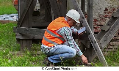 Construction worker checking wooden scaffolding and using tablet PC