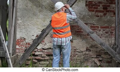 Construction worker checking wooden scaffolding