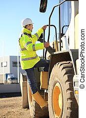 Construction worker climbing a wheel loader