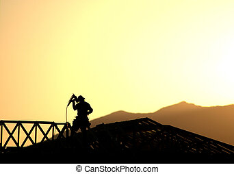 Construction worker framing a new home silhouetted against the evening sunset and mountains.