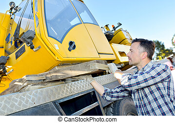 construction worker controls of lifting crane in truck