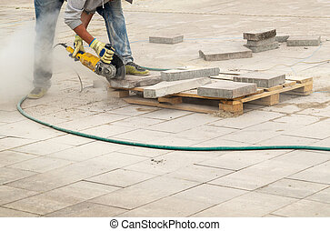 Construction worker cuts walkway curb with circular saw. Man Protect Hearing From Noise Hazards on the Job