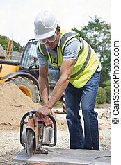 Construction Worker Cutting Stone With Circular Saw
