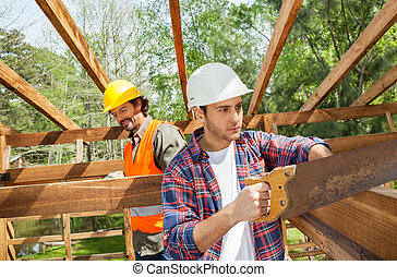 Construction Worker Cutting Wood With Handsaw At Site