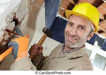 construction worker demolishing hole at a wall