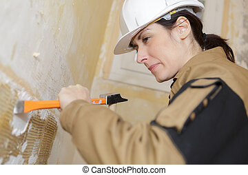 construction worker demolishing wall with a chisel