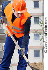 Construction worker digging sand with shovel, vertical