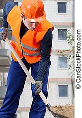 Construction worker digging sand with shovel, vertical