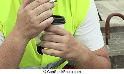 Construction worker drink coffee and smoking
