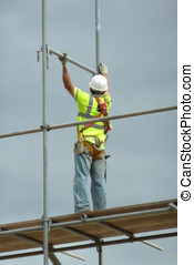 Construction worker erecting scaffolding on building site