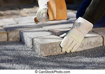Construction worker fixing a brick road
