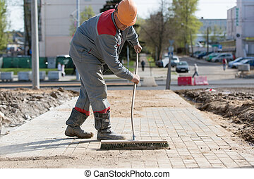 Construction worker grouting dry sand