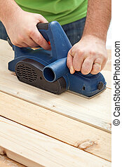 Construction worker hands with electric planer