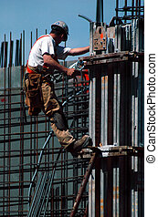 Construction worker hanging from a support beam