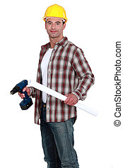 Construction worker holding a rolled-up plan and a battery-powered screwdriver