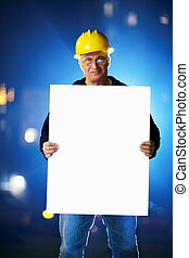 Construction worker holding blank white board. Shallow DOF.